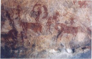 An image of a cave painting, an early example of art made from soil, in which cave people appear to be herding or hunting large mammals, possibly horses or cows.